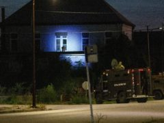 Illinois State Police in armoured trucks shine a spotlight on a building during a manhunt after a shooting in southern Illinois (Daniel Shular/St. Louis Post-Dispatch via AP)