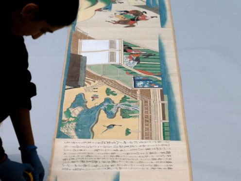 Collections digitisation assistant Ayesha Hussain measures one of three ancient Japanese scrolls (Joe Giddens/PA)