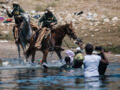US Customs and Border Protection mounted officers attempt to contain migrants as they cross the Rio Grande (AP Photo/Felix Marquez)