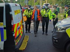 Officers lead a protester to a police van at a slip road at Junction 18 of the M25 (Steve Parsons/PA)