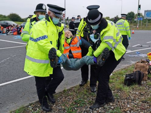 Police officers carry away a protester who had glued himself to the highway at a slip road at Junction 4 of the A1(M), near Hatfield (Steve Parsons/PA)