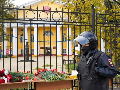 A police officer walks past flowers and candles displayed on a table outside the Perm State University following a campus shooting (AP Photo/Dmitri Lovetsky)