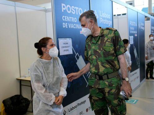 Rear Admiral Henrique Gouveia e Melo shares a joke with a military nurse during a visit to a vaccination centre in Lisbon (Armando Franca/AP)