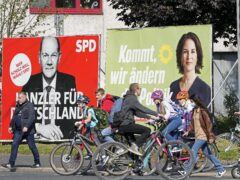 People walk and drive past election posters of the three chancellor candidates, from right, Armin Laschet, Christian Democratic Union (CDU), Annalena Baerbock, German Green party (Die Gruenen) and Olaf Scholz, Social Democratic Party (SPDD) (Martin Meissner/AP)