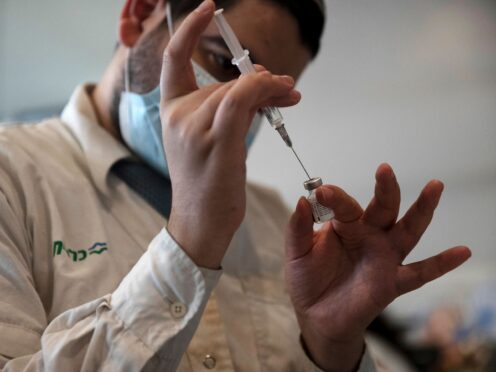 A medical worker prepares a vial of the Pfizer coronavirus vaccine at Clalit Health Service's centre in the Cinema City complex in Jerusalem (AP)