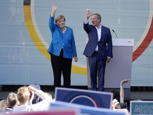 Chancellor Angela Merkel and Governor Armin Laschet wave to supporters at an election campaign event (Martin Meissner/AP)