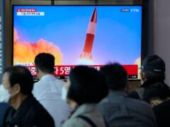 People watch a TV showing a file image of North Korea's missile launch during a news program at the Seoul Railway Station in Seoul, South Korea (Ahn Young-joon/AP)