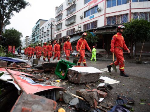 Rescue workers walk near debris in Luxian in the aftermath of the earthquake (Jiang Hongjing/Xinhua via AP)