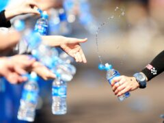 Volunteers offer runners water during the London Marathon (PA)
