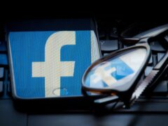The logo of social networking site Facebook is seen reflected on the screen of a smartphone and a pair of glasses resting on a laptop keyboard. PRESS ASSOCIATION Photo. Picture date: Sunday March 25, 2018. Photo credit should read: Dominic Lipinski/PA Wire