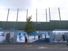 A woman walks past a Belfast peace wall (Niall Carson/PA)