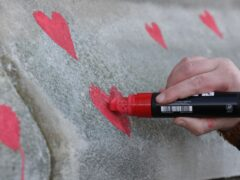 Members of bereaved families paint red hearts on the Covid-19 Memorial Wall opposite the Houses of Parliament (Lucianna Guerra/PA)