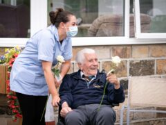 """Health care assistant Rose Waddington and 98-year-old resident John Kykot with """"thank you"""" white roses that were presented to them at Norwood House Nursing Home in Keighley, Yorkshire (Danny Lawson/PA)"""