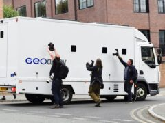 Photographers take pictures through the windows of a prison van carrying Manchester City footballer Benjamin Mendy as it leaves Chester Magistrates' Court, Chester in August (PA)
