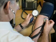 A GP checking a patient's blood pressure. GPs and other medics are feeling burnt out (Anthony Devlin/PA)