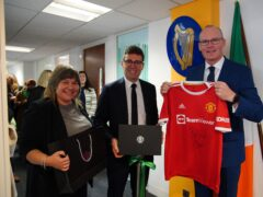 Foreign Affairs Minister Simon Coveney being presented with a signed Denis Irwin Manchester United FC shirt by Stockport Council Leader Elise Wilson and mayor of Greater Manchester, Andy Burnham, in Manchester, at the official opening of the Consulate General of Ireland for the North of England (Peter Byrne/PA)