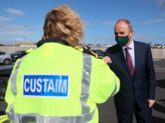 Taoiseach Micheal Martin is greeted by a customs official at Rosslare Europort, Co Wexford (Brian Lawless/PA)