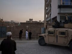 Afghans watch as Taliban fighters ride atop a humvee after detaining four men who got involved in a street fight in Kabul, Afghanistan (AP)