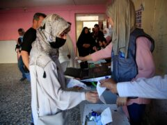 Iraqis queue to cast their votes at a polling station in the country's parliamentary elections in Baghdad (Hadi Mizban/AP)