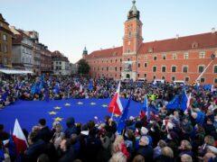 Demonstrators wave European Union and Polish flags in support of EU membership during a demonstration in Warsaw (Czarek Sokolowski/AP)