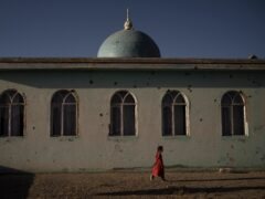 An Afghan girl walks outside a mosque marked by bullet holes at a village in Wardak province, Afghanistan (Felipe Dana/AP)