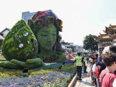 Tourists pass a floral decoration celebrating the UN Biodiversity Conference in China (Chinatopix via AP)