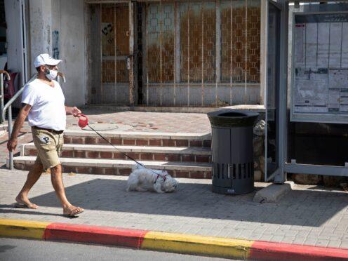 A man walks a dog near the talking bin (Sebastian Scheiner/AP)