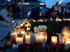 Flowers and candles are placed at the scene of an attack (Terje Bendiksby/NTB via AP)