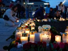 Flowers and candles are placed at the scene of the attack in Kongsberg, Norway (NTB via AP)