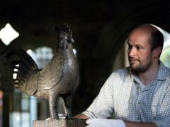 Archivist Robert Athol with a bronze statue of a cockerel called The Okukor, which will be returned from Cambridge's Jesus College to the Court of Benin in southern Nigeria on October 27 (Joe Giddens/PA)