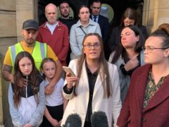 Tia Skelton, centre, the sister of Lewis Skelton, is surrounded by members of their family and solicitor Neil Hudgell, left, as she reads a statement to the media outside Hull Coroner's Court (Dave Higgens/PA)