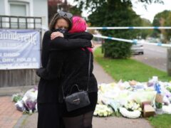 People hug at the scene near Belfairs Methodist Church in Leigh-on-Sea, Essex, where Conservative MP Sir David Amess was killed (Kirsty O'Connor/PA)