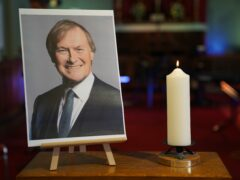 A candle and a photo of Sir David Amess greeted mourners at a vigil in Essex (Kirsty O'Connor/PA)