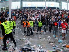 Stewards replace barricades after they were knocked over by supporters outside Wembley during the Euro 2020 final (David Cliff/AP)