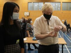 Prime Minister Boris Johnson shakes a dose of the Pfizer vaccine (Matt Dunham/PA)