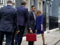 Chancellor Rishi Sunak holds his ministerial 'Red Box' as he stands with his ministerial team and parliamentary private secretaries, outside 11 Downing Street (PA)