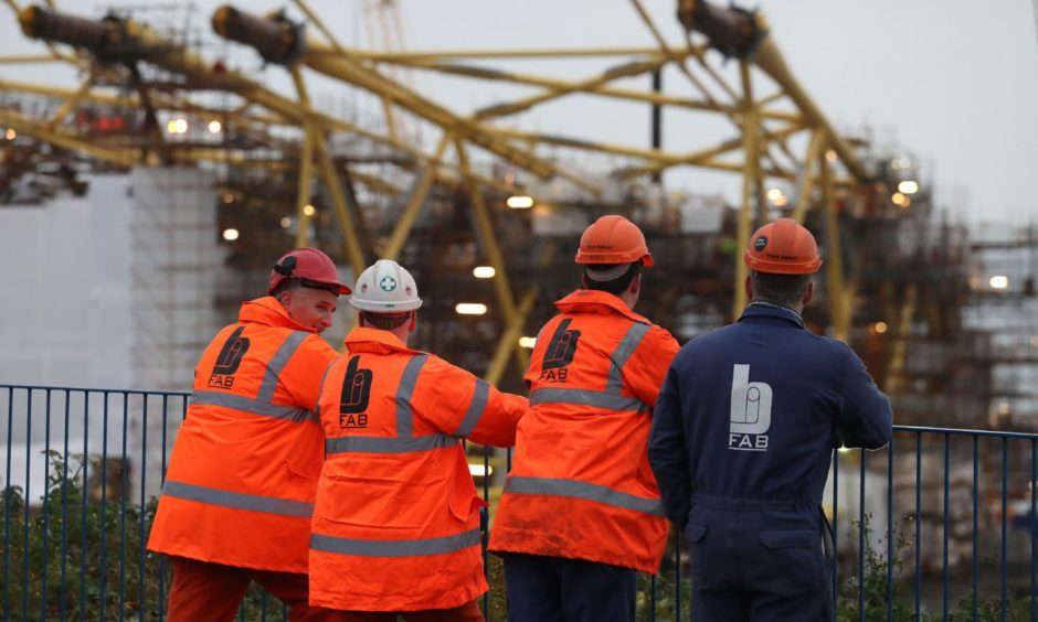 Workers at BiFab look on at turbine jackets.