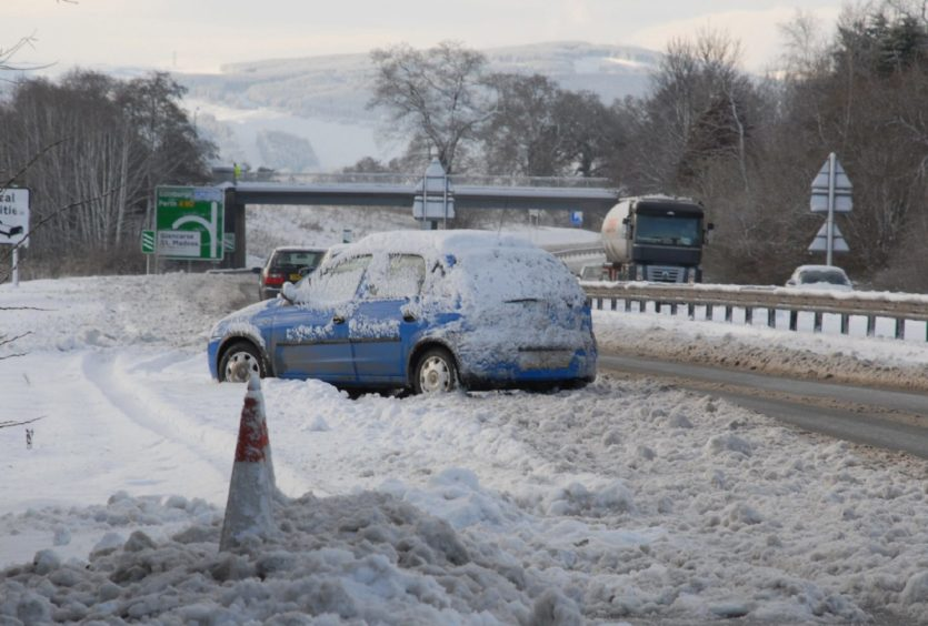 An abandoned car blocks the inside lane of the westbound carriageway of the A90 near Glencarse.