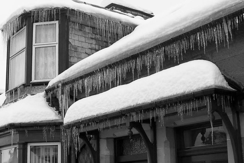 A house on Jeanfield Road, Perth, becomes a black-and white layer cake of icicles.