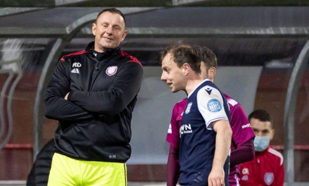 Dundees Paul McGowan shares a joke with Arbroath goalie coach Rab Douglas.