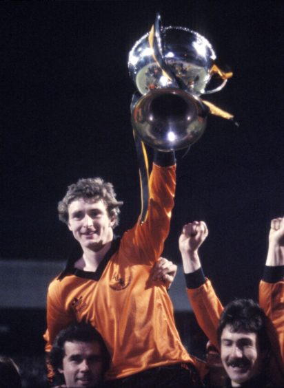 Dundee Utd's Paul Hegarty raises League Cup trophy as team-mates carry him on their shoulders.
