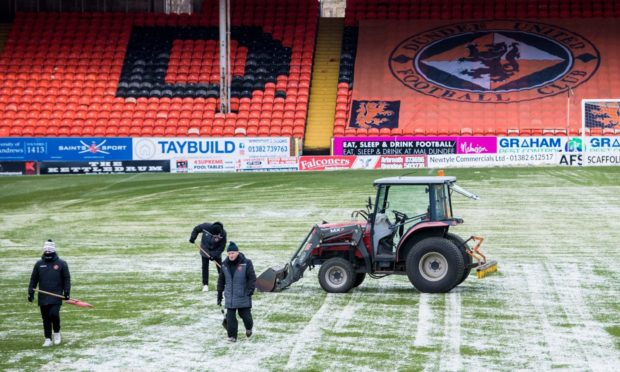 Dundee United staff get to work on frozen pitch.