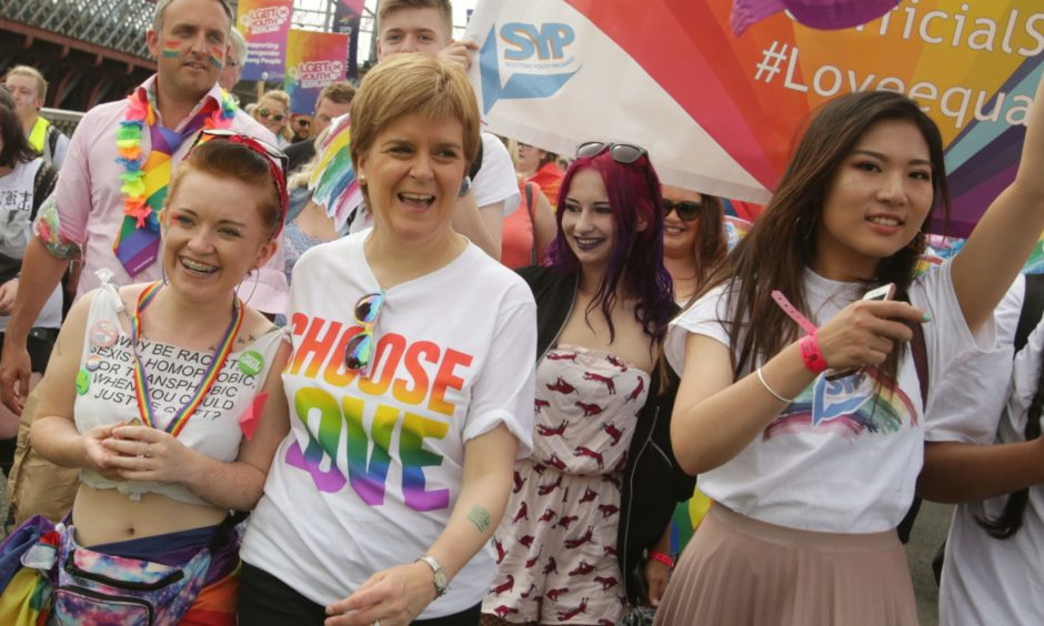 Nicola Sturgeon wearing a T-Shirt saying 'Choose Love', surrounded by people at a Pride march