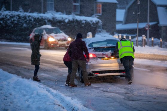 Good Samaritans helping to push cars on an icy curve off Glasgow Road, Perth.