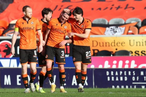 Dundee United players celebrate with Adrian Sporle.