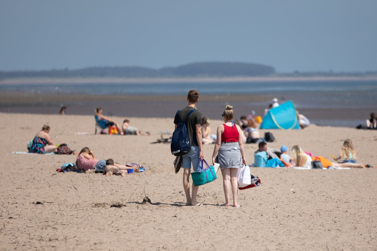 A couple looking for a place to sit on a busy Broughty Ferry beach