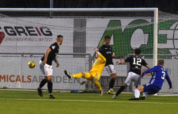 Harry Milne scores for Cove in their fixture against Montrose in December.