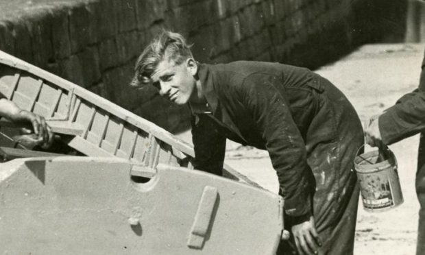 Prince Philip doing boat maintenance at Hopeman Harbour while a Gordonstoun pupil.