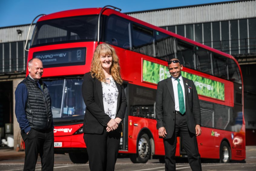 Keith Watson, Christine McGlasson and Johnathan Eggleton standing next to an electric bus bound for Lochee Road