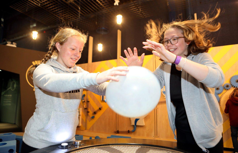 Flo Steadman and Ashlyne Johnstone play with a balloon on the air machine.